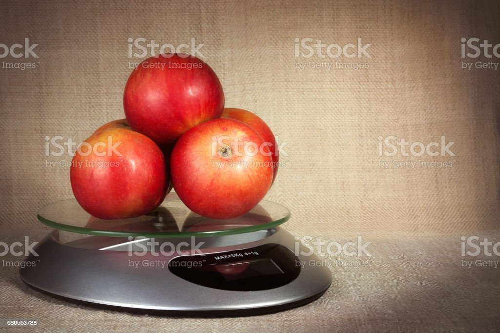 Red apples on the kitchen scales on a brown background zbiór zdjęć royalty-free