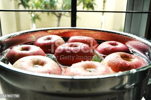 Fresh red apples floating on water beside kitchen window