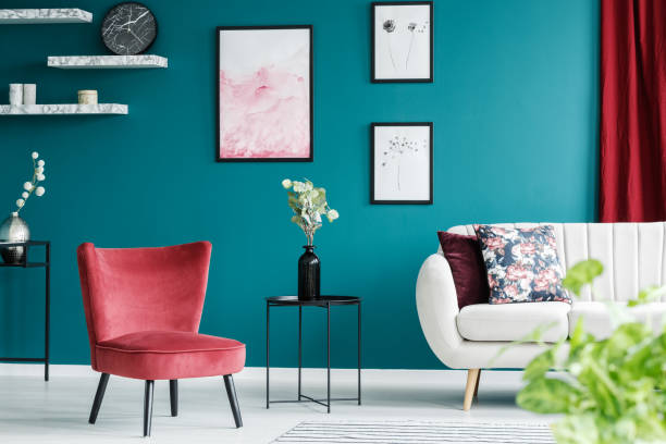 Red armchair in living room Red armchair, white sofa, paintings and black table in a green living room interior multi colored stock pictures, royalty-free photos & images