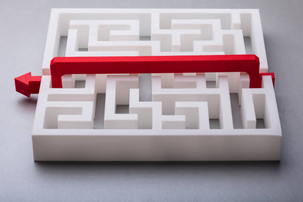 red arrow crossing over white labyrinth - maze stock photos and pictures