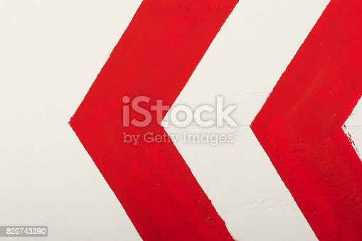 istock Red arrow indicates direction to the left painted with paint on a white wall 820743390