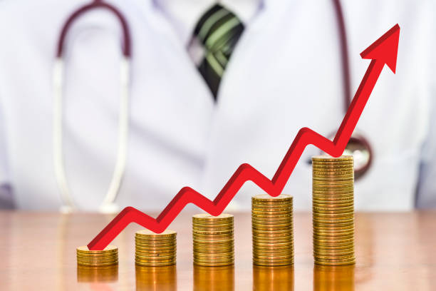 Roter Pfeil über Stapel von Geld Münzen angeordnet wie ein Graph auf Holztisch mit verschwommenen Arzt Stethoskop um Hals eine Szene in den Rücken, Konzept der finanziellen Gesundheit – Foto