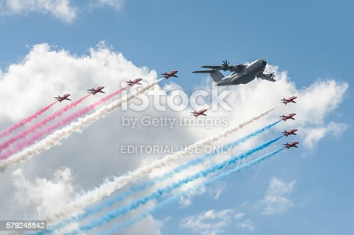 Farnborough, UK - July 17, 2016: RAF Red Arrows flying display team and an Airbus A400 transporter in formation in the skies over Farnborough, UK