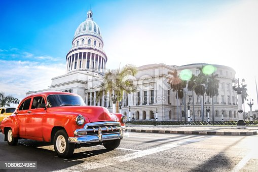 Red Authentic Vintage Car Moving In Front Of El Capitolio In Havana, Cuba