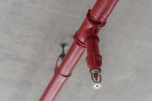 """A sprinkler is a device commonly used in firefighting. It is made up of an """"armor"""", a sensitive element called a bulb. The sprinkler nozzle is threaded to a pressurized piping and remains closed by a cap locked by the bulb. Inside the bulb a liquid expands at a certain temperature so that the capsule will rupture when a fire starts, releasing the water to fight."""