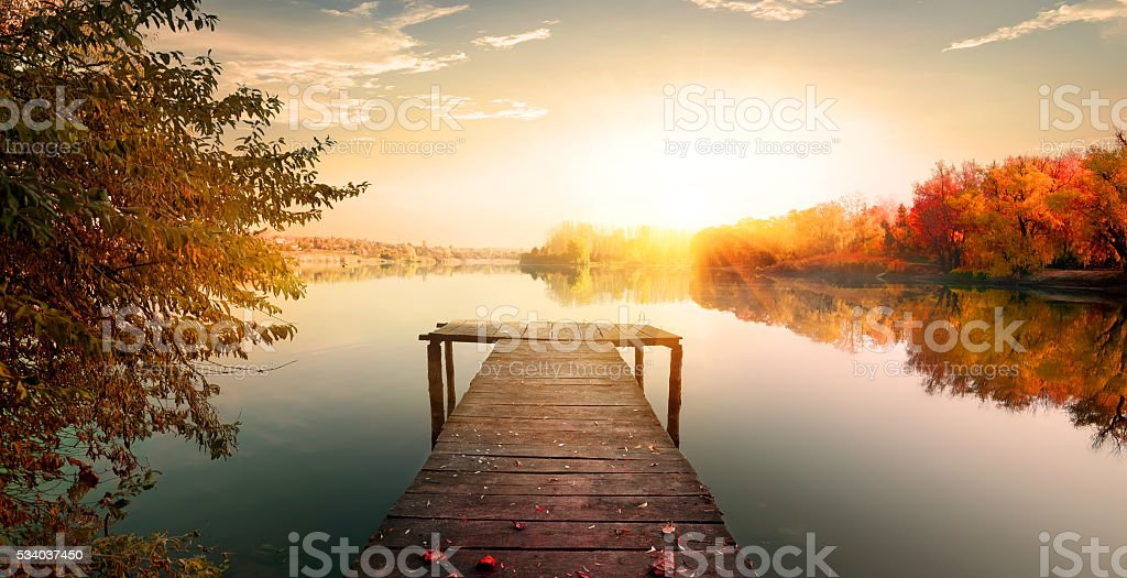 Red autumn and wooden fishing pier on river