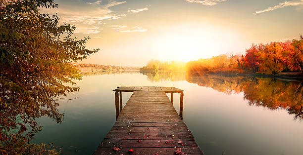 Red autumn and fishing pier Red autumn and wooden fishing pier on river tranquil scene stock pictures, royalty-free photos & images