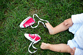 Red baby toddlers sneakers and white woman sneakers on the grass with little baby feet