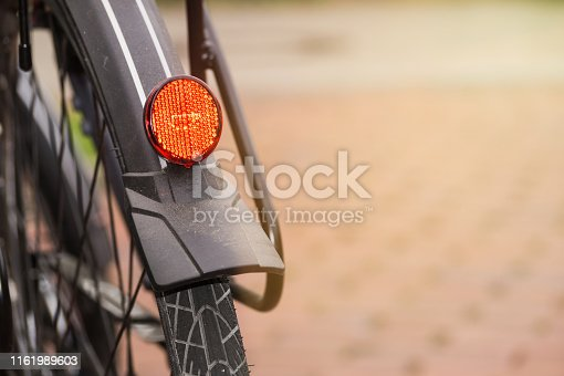 A red Backlight and red Safety Reflector of a modern City Bike. Close up.