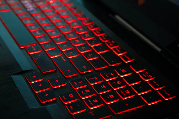 Red backlight on a modern keyboard of gaming laptop in the dark stock photo