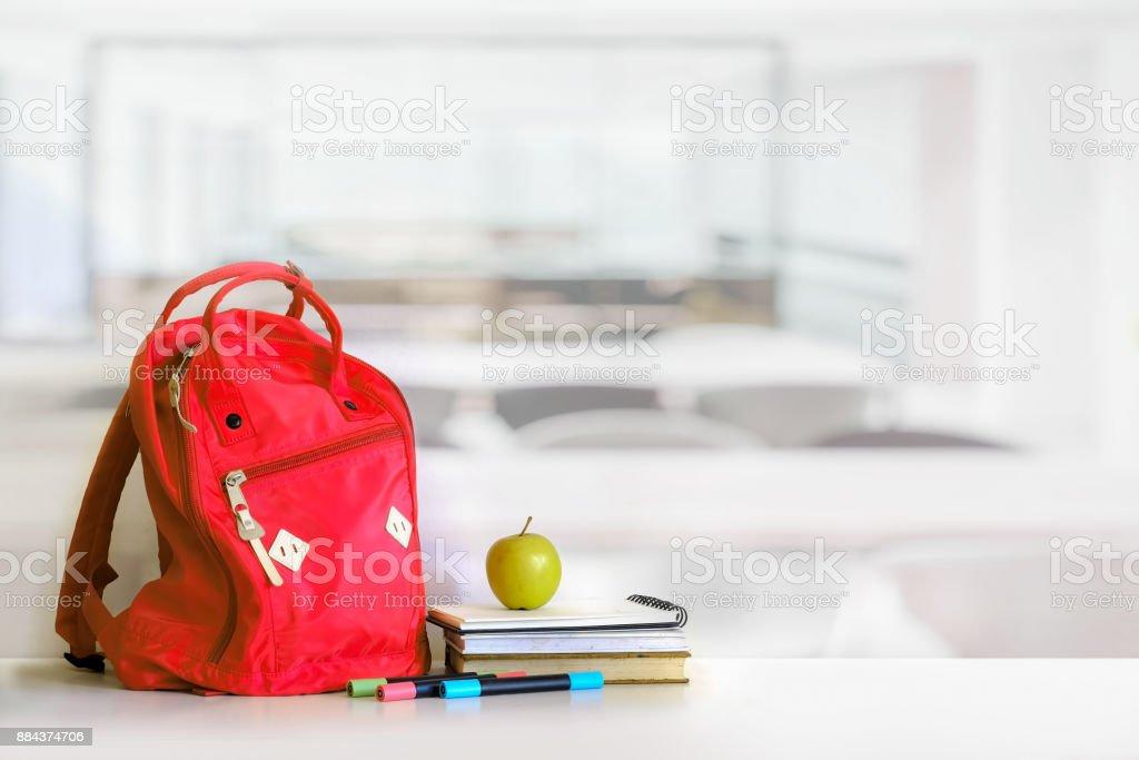 赤いバックパックや書籍の学校は教室で提供します。 ロイヤリティフリーストックフォト