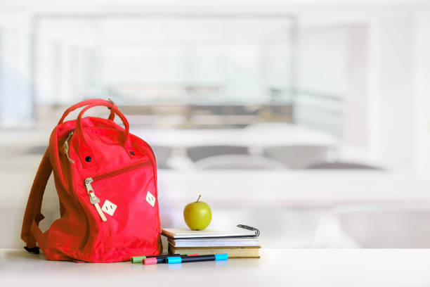 Red backpack and books school supplies in classroom. stock photo