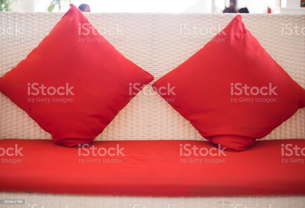 Red backrest pillow on the white sofa bed. stock photo