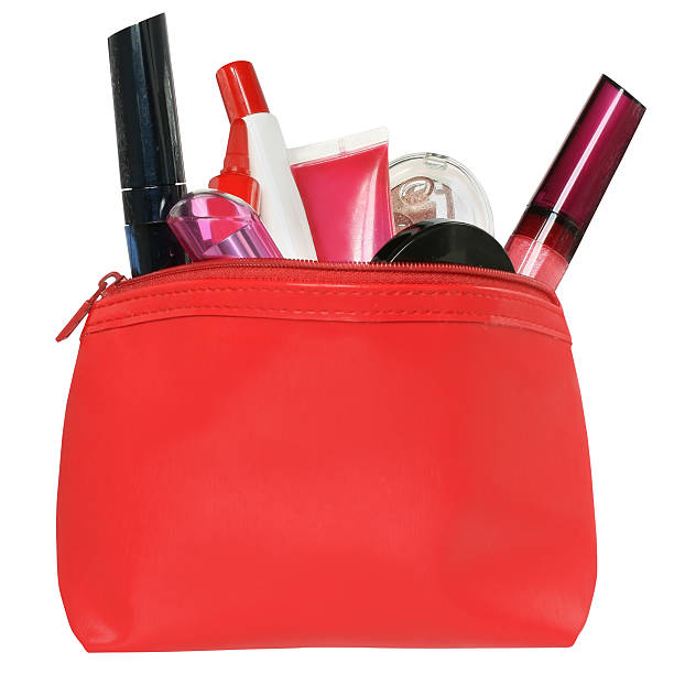 Borsa rossa per i prodotti cosmetici con un make-up accessori. - foto stock