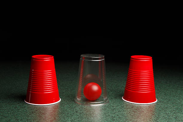 Red Ball Hidden Under Clear Cup Life is easy when you know the answers.  Location of red ball is revealed by clear cup.  Copy space in upper half of the frame fades to black.  This concept photo could be applicable to many concepts including – risk, reward, seeking answers, finding solutions, decision making, gaming, and many others. shell game stock pictures, royalty-free photos & images