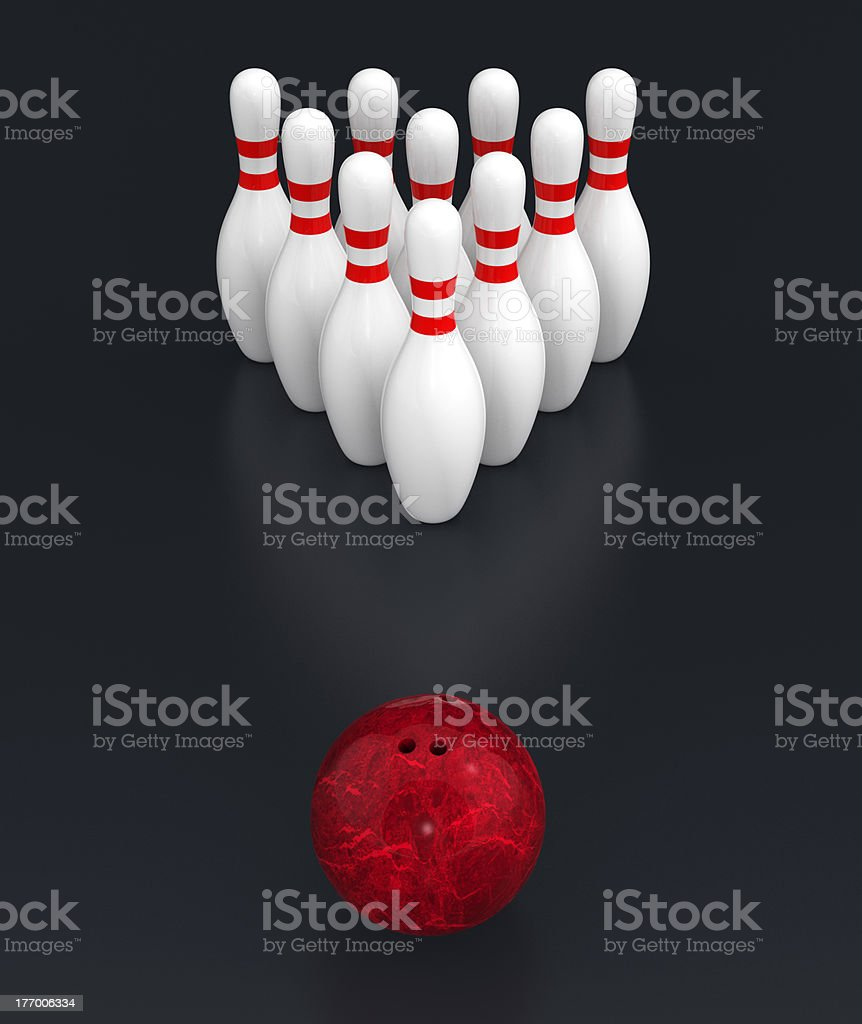 a red ball moving toward to bowling pins on dark background.