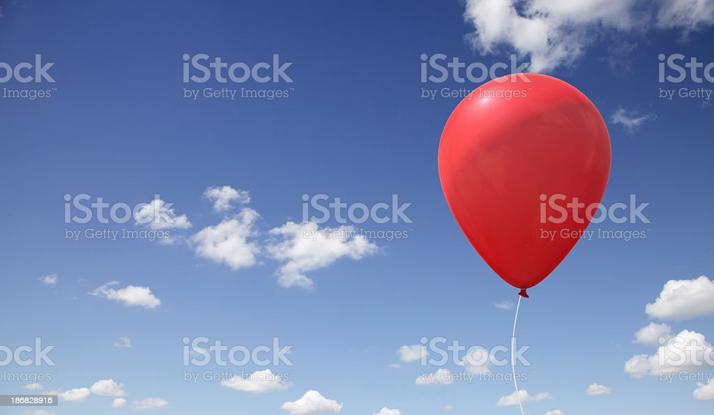 A red balloon under a blue sky stock photo