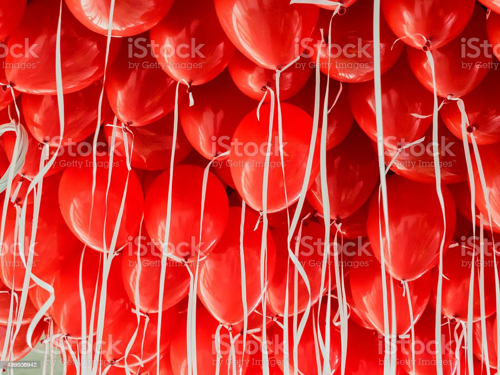 Red balloons hanging under a ceiling stock photo