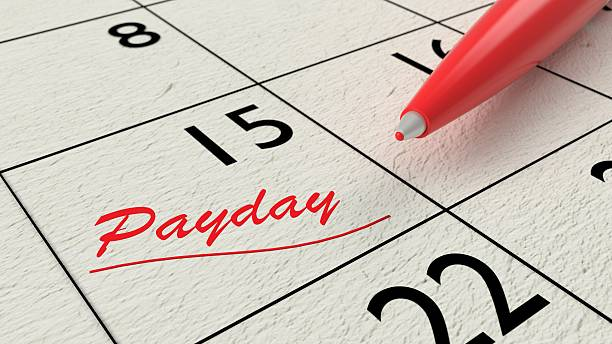 red ballpen on a paper calendar closeup - wages stock photos and pictures