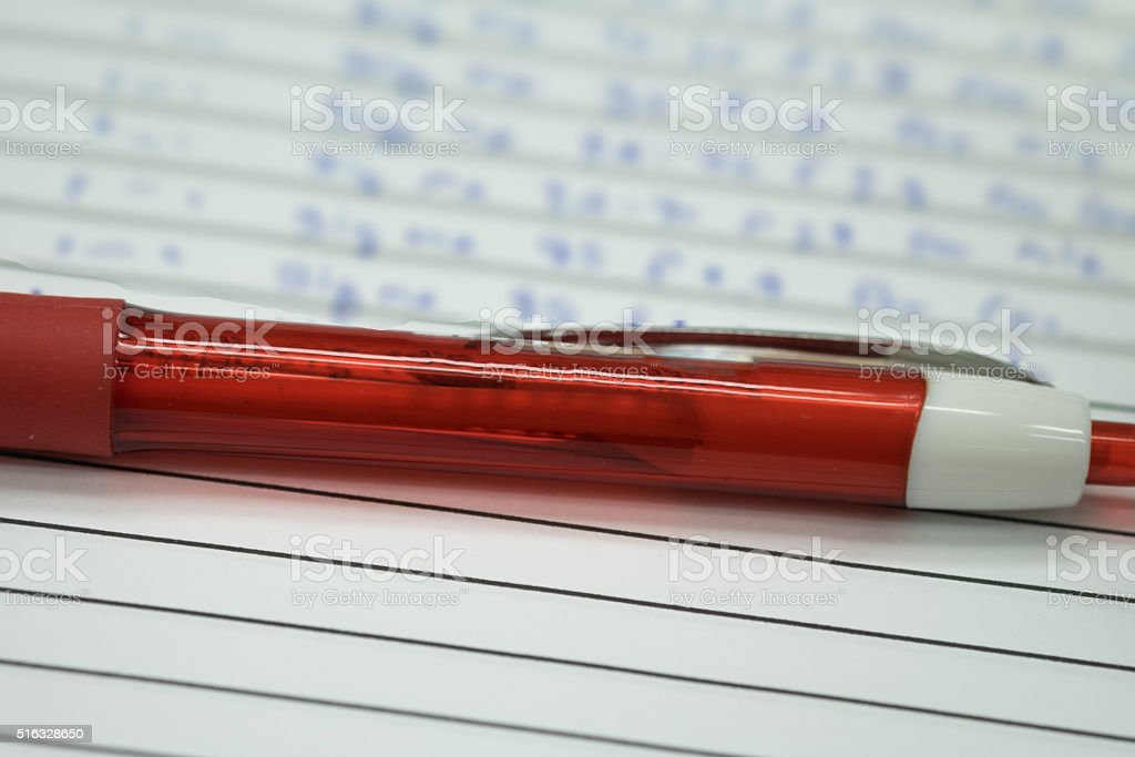 Red ballpen on white notebook stock photo