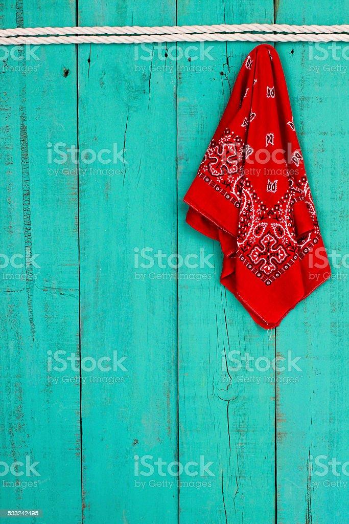 Red bandana hanging on rope on wood background stock photo