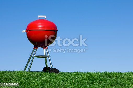 Red Generic Brand Barbecue Grill against a Blue Sky with Four Legs
