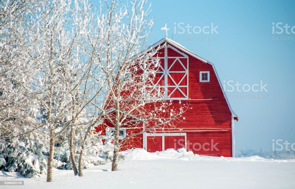 Red barn and snow covered field    blue sky stock photo