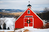 A small red barn, nestled in the highlands, is decorated for Christmas