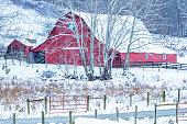 Red barn contrasting against winter landscape