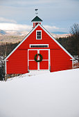 A red barn is decorated with a Christmas wreath in the highlands of New England