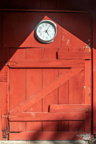 Red barn door wood background with clock, copy space, letter z, no people. stock photo