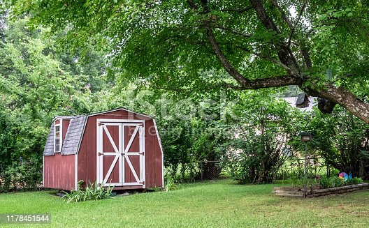 Red barn shed/farmhouse in green wooded area in yard.