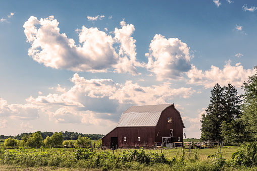Country landscape of dramatic cumulus clouds over a red barn in the midwestern United States.