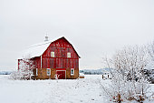 Fresh snow surrounds an old red barn in rural Wisconsin.