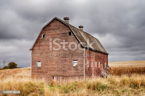 An old red barn stands next to a field in the Palouse countryside near Oakesdale, Washington.