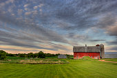 A country Red barn and summer evening cloudscape in rural Minnesota. This photo includes farm silos and sheds with green grass in the foreground. I used a wide angle 14-24 mm lens to help with the framing of this landscape shot.