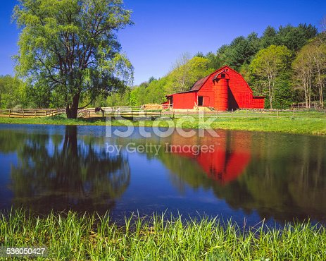 Red barn nestled in the Green Mountains of Vermont with reflection in the still waters of a pond