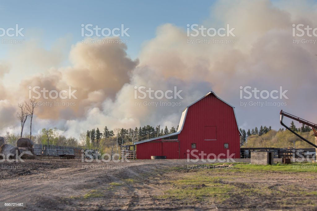 red barn with a cloud of smoke stock photo