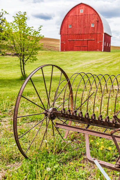 Red barns and antique farm equipment in the Palouse hills. stock photo