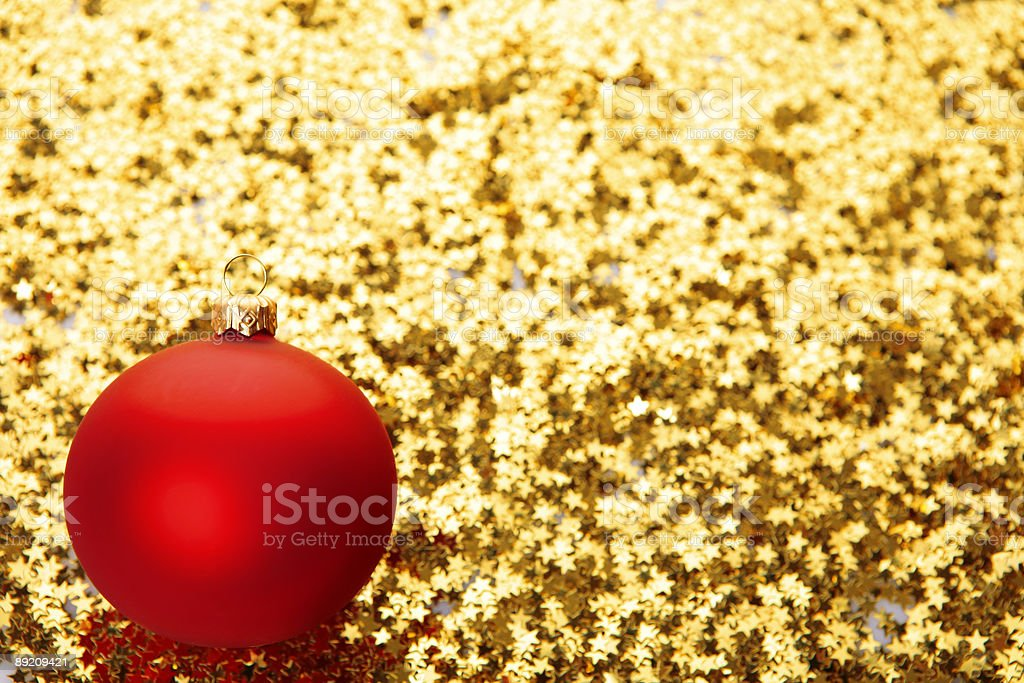 red bauble on golden stars background stock photo