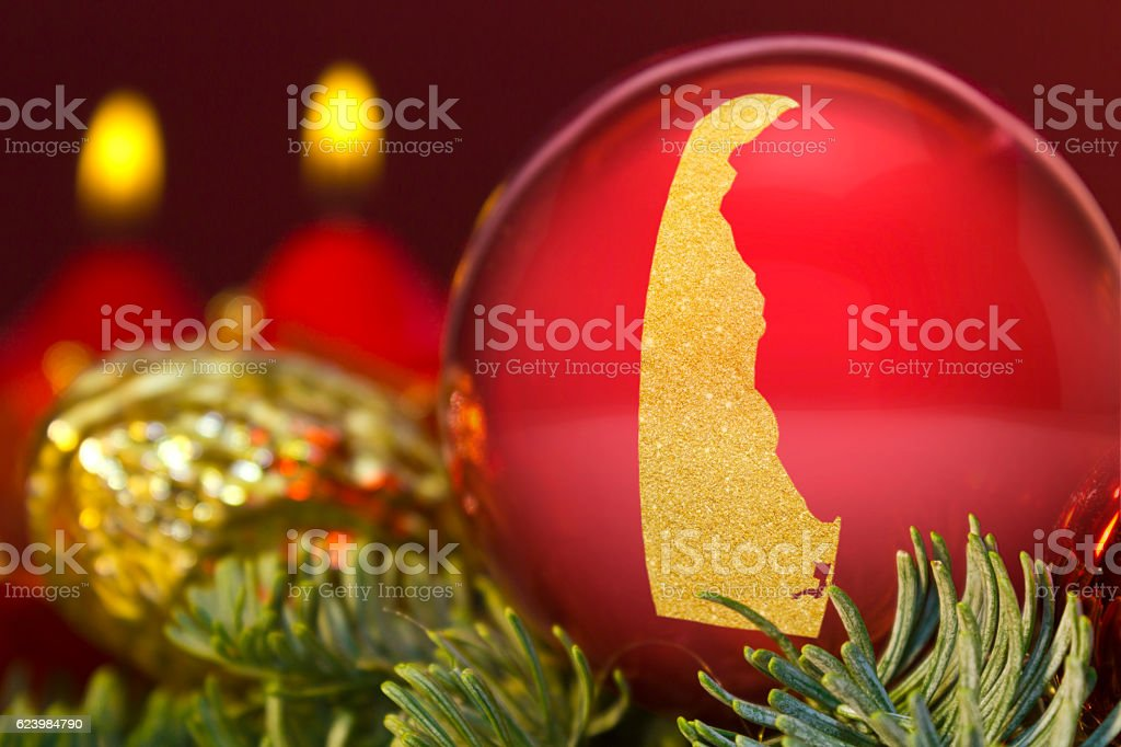 Red bauble with the golden shape of Delaware.(series) stock photo
