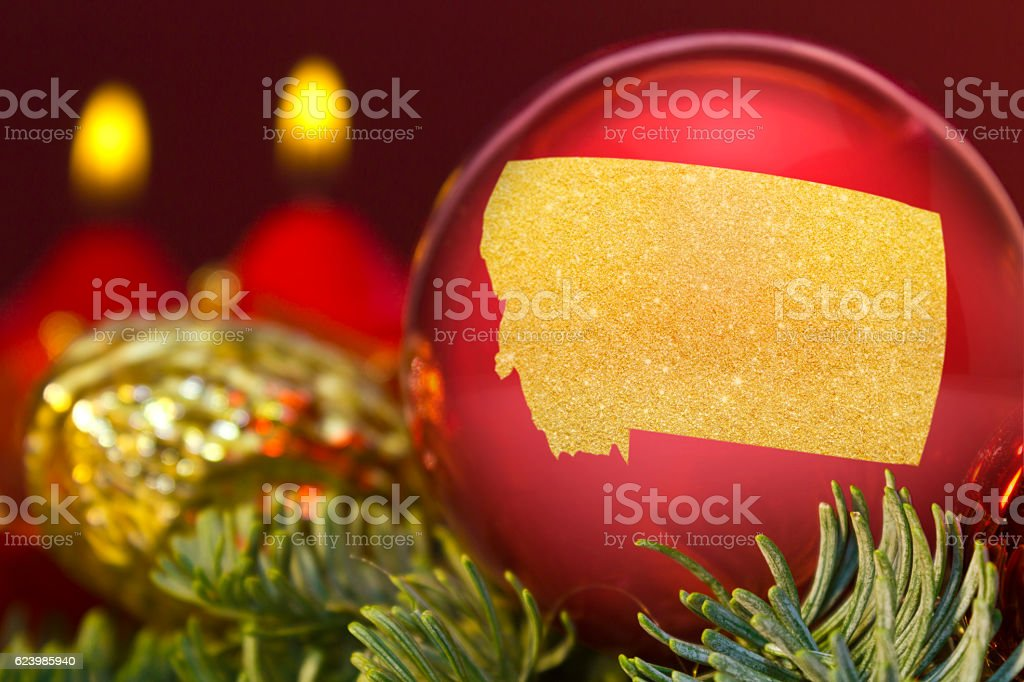 Red bauble with the golden shape of Montana.(series) stock photo