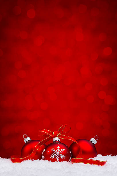 Red bauble withs snowflake decoration lying on snow stock photo