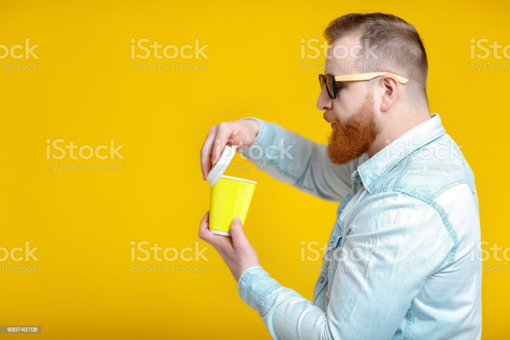 red beard man in sunglasses and denim shirt holding paper cup with...