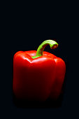 istock Red bell pepper on black background 1281637665