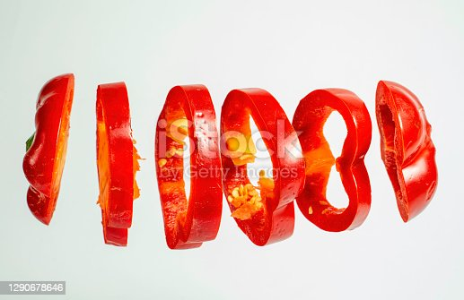 Red bell pepper slices floating isolated on white background