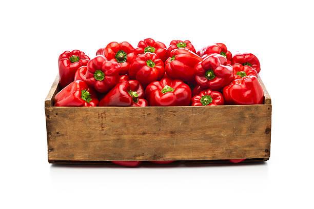 campainha pimentos vermelhos em uma caixa de madeira, isolado no branco - red bell pepper isolated imagens e fotografias de stock