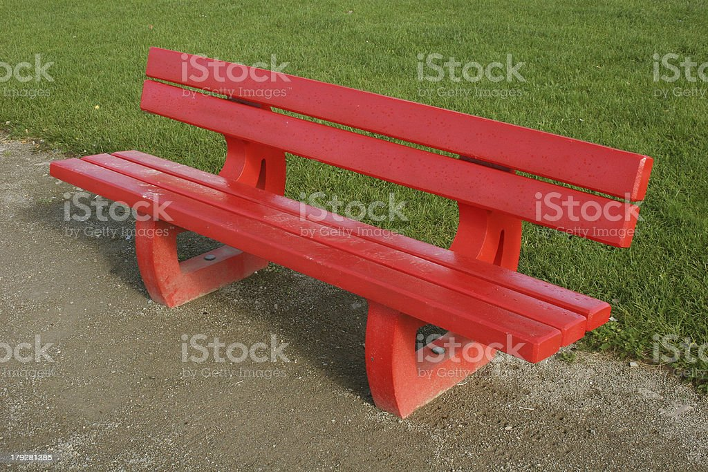Red bench in front of green grass stock photo