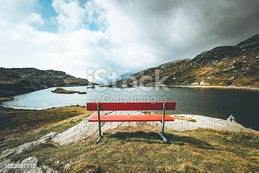 red bench at 2066m above sea level at the san bernardino pass in switzerland, europe.