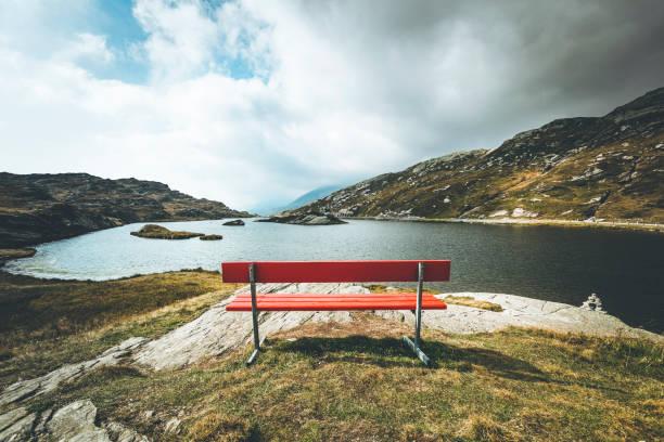 röd bänk med en vy, mountain lake san bernardino, schweiz - bench bildbanksfoton och bilder